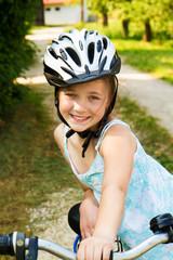 Bambina sorridente in bicicletta