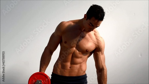 Young handsome male bodybuilder training obliques with dumbbell