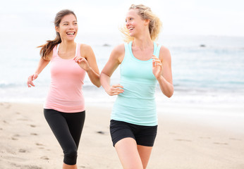 Women running jogging training happy on beach