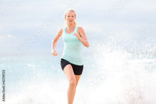 Running woman athlete jogging on beach