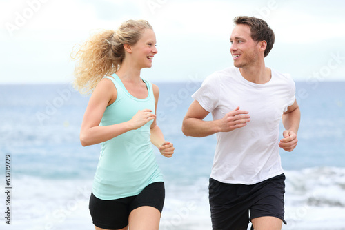 Running couple jogging exercising on beach talking