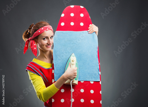Smiling housewife with ironing-board