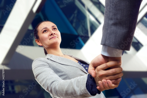 Cheerful businesswoman  and client handshaking