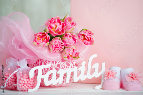 Pink tulips, baby shoes and family sign
