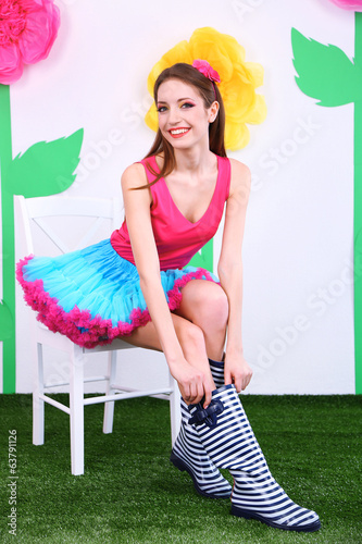 Beautiful young woman in petty skirt sitting