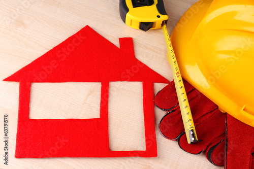 House of felt with helmet and gloves on wooden background