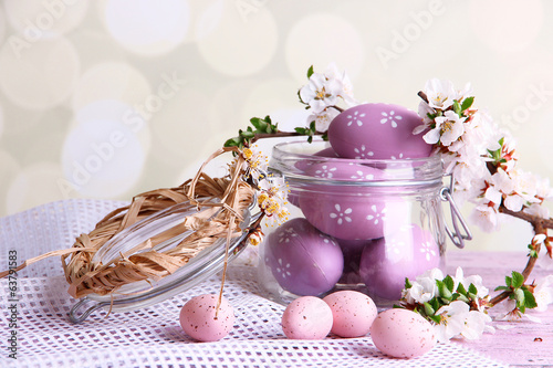 Composition with Easter eggs in glass jar and blooming branches