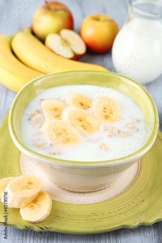 Tasty oatmeal with bananas and milk on wooden table