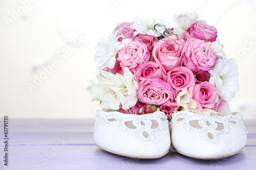 Beautiful wedding bouquet and shoes on table on light