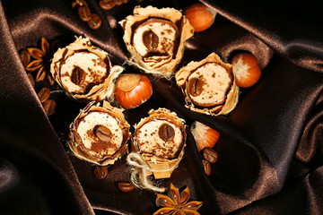 Tasty chocolate candies with coffee beans and nuts on silk
