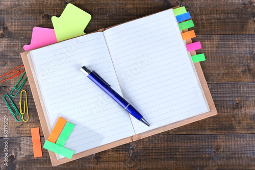 Notebook, pen, and stickers on wooden background