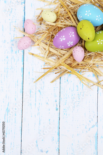 Easter composition with straw on wooden table close-up