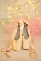 Ballet pointe shoes on floor on bokeh background