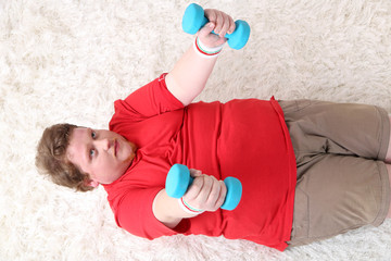 Large fitness man making exercises with dumbbells