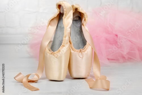 Ballet pointe shoes on floor in dance hall