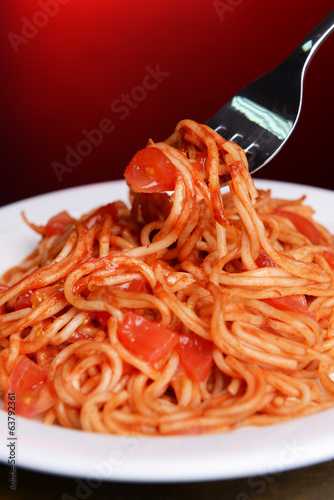 Pasta with tomato sauce on plate on table on red background