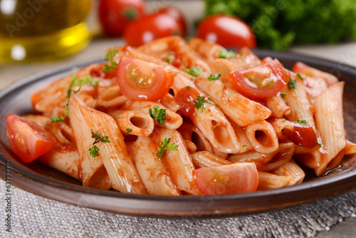 canvas print picture Pasta with tomato sauce on plate on table close-up