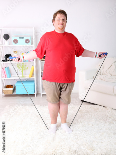 Large fitness man working out with skipping rope, at home