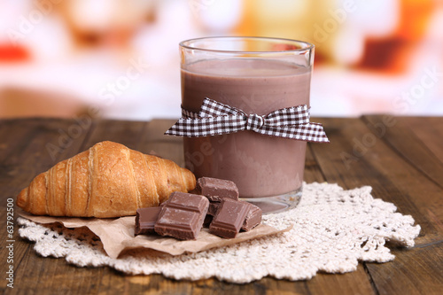 Chocolate milk in glass, on wooden table, on bright background
