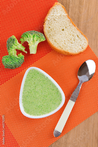Bowl of broccoli soup on table close up