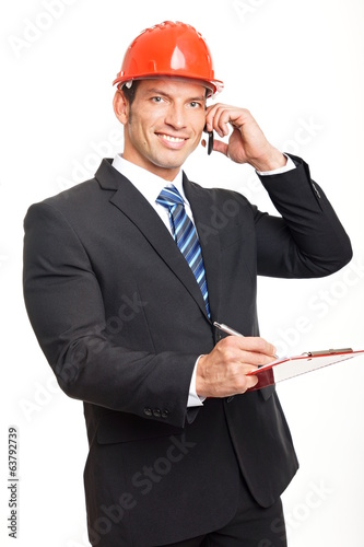 Handsome businessman in a helmet writes some document