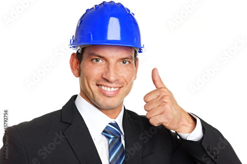 Handsome businessman in a protective helmet shows you thumbs up