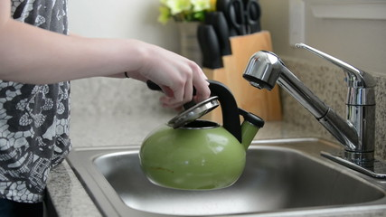 Person fills tea kettle in sink