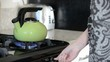 Person places tea kettle on stove
