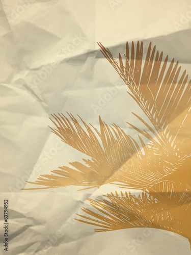 Gold palm leaf on white crumpled paper texture