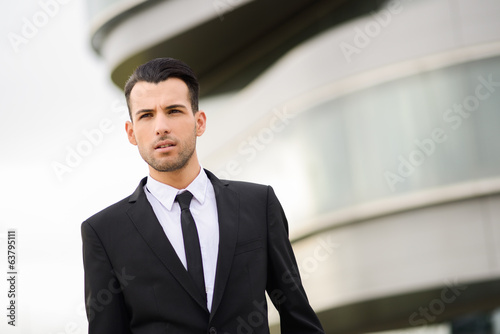 canvas print picture Young businessman near a office building