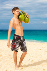 Happy handsome young male beach smiling at camera holding coconu