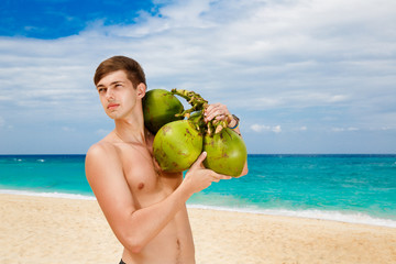 Happy handsome young male beach holding coconuts under the sun o