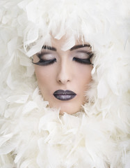 Beauty con piume bianche e occhi chiusi