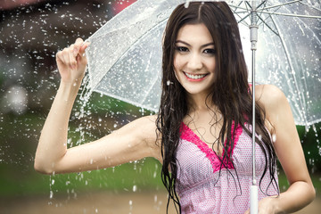 Beautiful girl in the rain with transparent umbrella