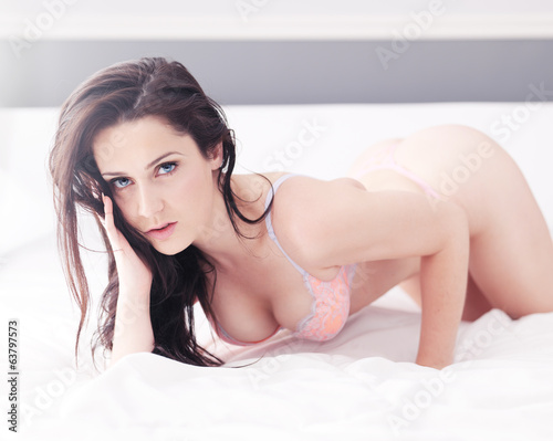 sexy blue eyed brunette posing on bed