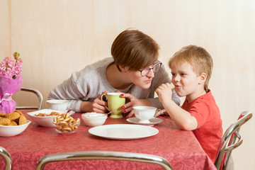 The small boy and his mother eat pancake