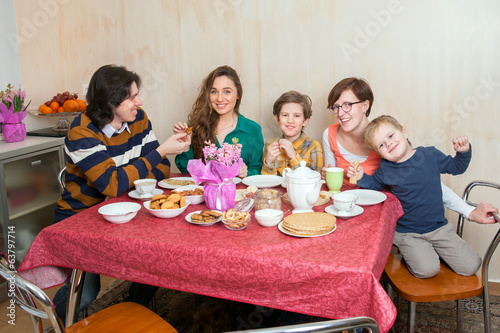 Two boys and three adults sit at the sweet table