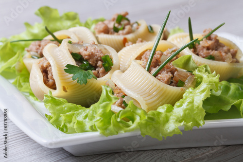 Pasta lumakoni stuffed meat and onion closeup