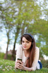 Jolie femme brune écoutant de la musique allongée dans l'herbe