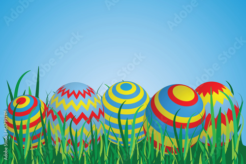 Colorful Easter Eggs on a row in Grass with Blue Sky