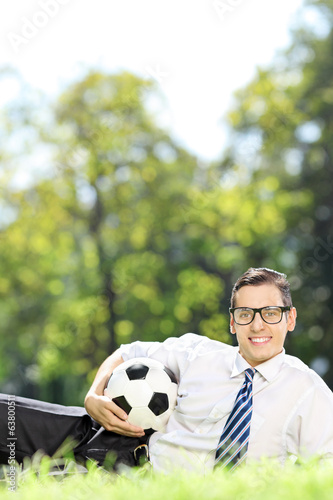 Young man with soccer ball lying in park