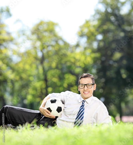 Young man lying in park and holding a football