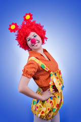Happy woman clown on blue background