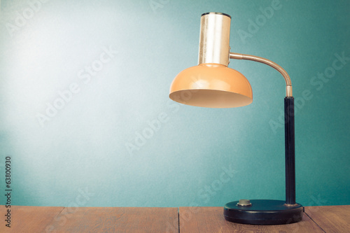 Retro orange desk lamp on wooden table