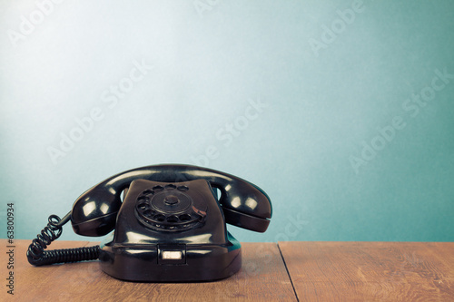 Retro black telephone on table front mint green background