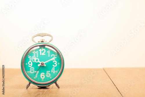 Old retro alarm clock on table