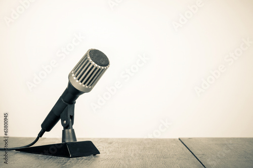 Retro style microphone on table sepia photo