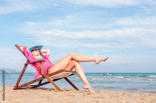 Girl sitting on a chair on the beach