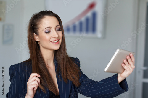 Attractive young businesswoman with tablet