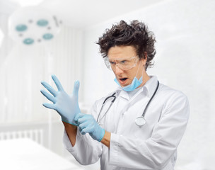 Funny doctor is putting on gloves